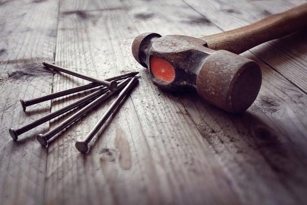 bigstock-Hammer-and-nails-on-floorboard-158701190.jpg